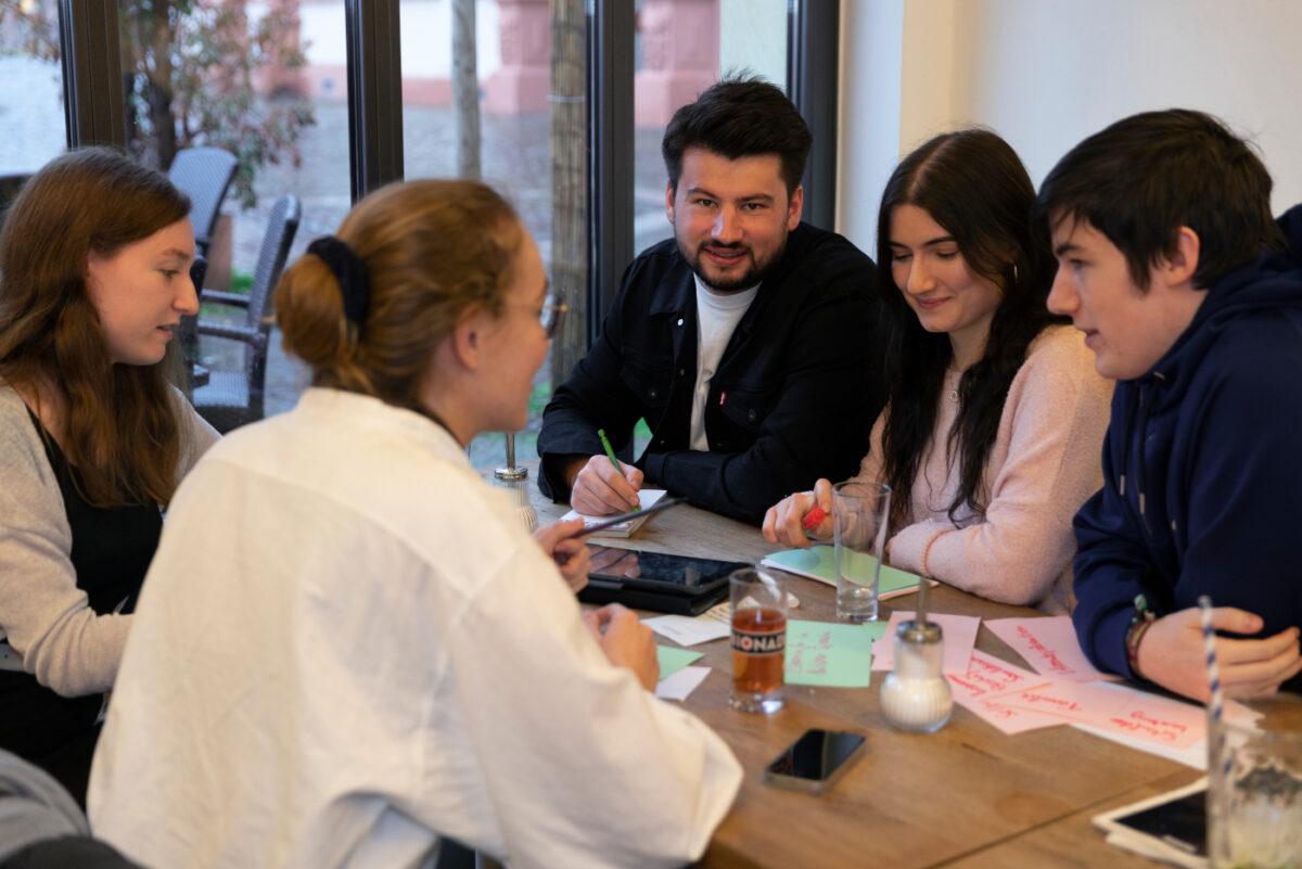 Foto von Fabian Ehmann und vier weiteren Personen. Alle Personen sind um einen Tisch versammelt und erarbeiten Ideen.