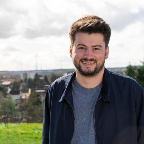 Foto von Fabian Ehmann. Fabian lächelt in die Kamera, im Hintergrund sind Weinberge sowie eine Stadt sichtbar.