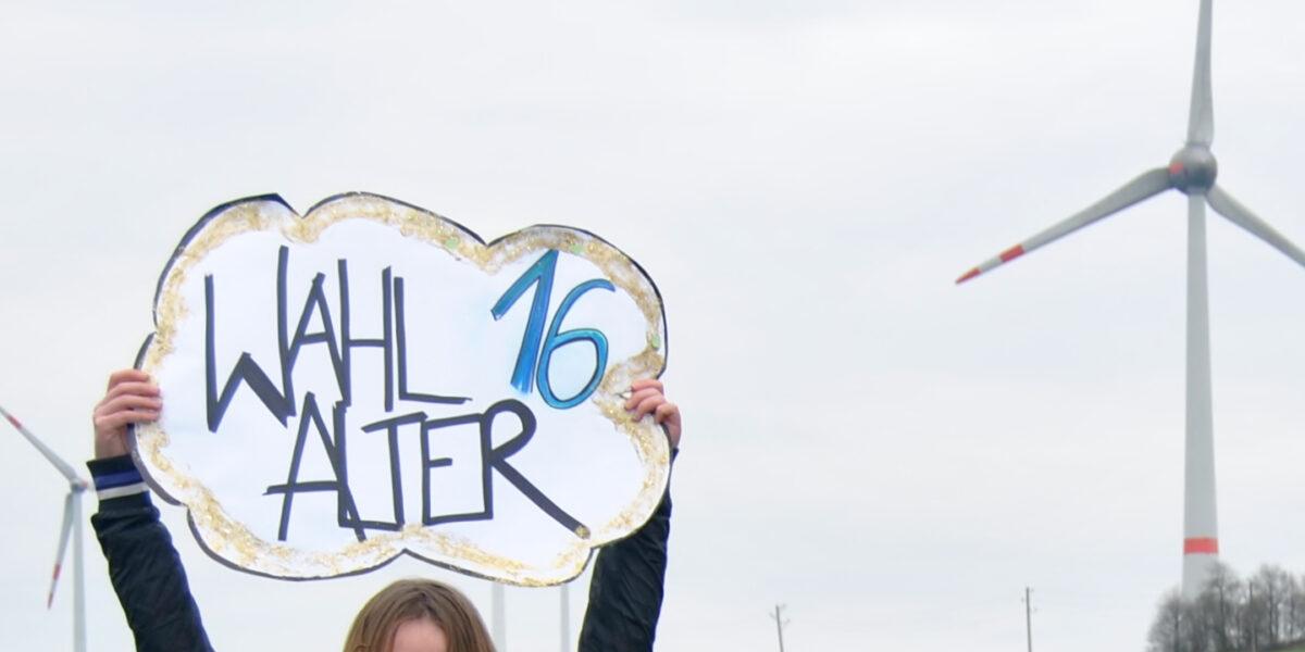 """Eine Person hält ein Schild mit der Aufschrift """"Wahlalter 16"""" hoch, im Hintergrund stehen Windräder."""